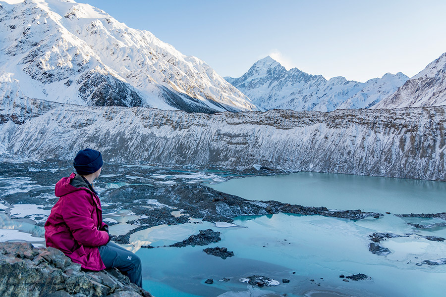 A student looks out on a snowy Mt. Cook in New Zealand.